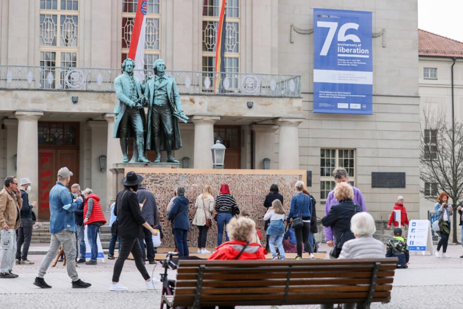 Zahlreiche Menschen stehen vor dem Theaterplatz mit dem Goethe-Schiller-Denkmal in Weimar. Die kreisfreien Städte Weimar und Suhl sind in Thüringen wieder die ersten beiden Gebiete mit einer Inzidenz unter 100.