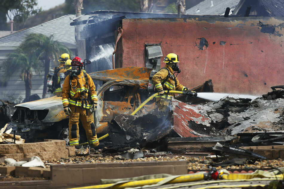 Firefighters put out hot spots at the scene of the fatal plane crash on Monday.