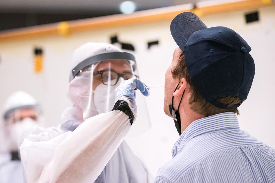 Ein Reisender (r) lässt am Flughafen von einem Mitarbeiter des Deutschen Roten Kreuzes (DRK) einen Corona-Test machen.