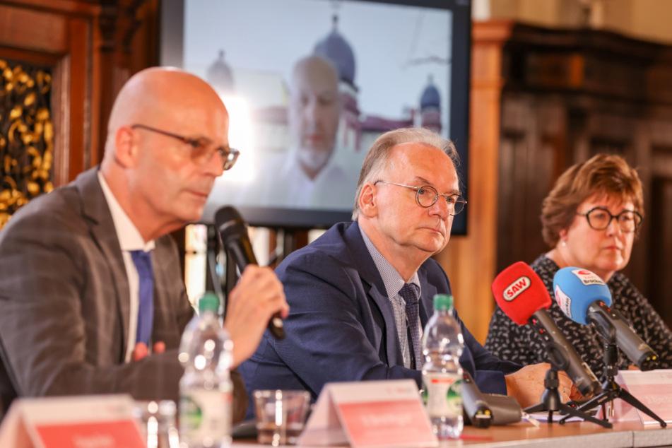 Halles Oberbürgermeister Bernd Wiegand (links) berät mit Petra Grimm-Benne (SPD), Sozialministerin Sachsen-Anhalt, und Reiner Haseloff (CDU), Ministerpräsident von Sachsen-Anhalt, über die Planung für das erste Jahresgedenken des Attentats von Halle. Max Privorozki, Präsident der Jüdischen Gemeinde Halle, ist per Video zugeschaltet.