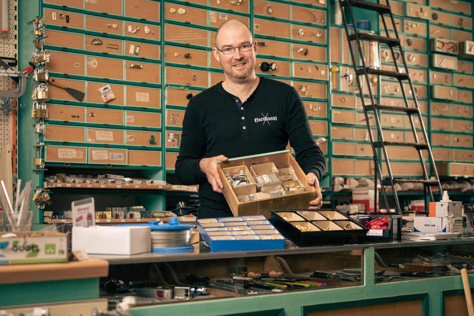 """Thomas Haaß (44) führt jetzt den Traditionsladen, benannte ihn in """"Eisenfeustel"""" um. Materialschrank und Leiter im Hintergrund sind noch echte Originale."""
