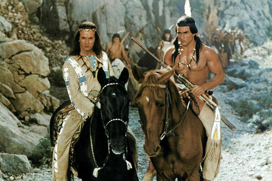 """Gojko Mitic (r.) als durchtrainierter und schöner Indianer an der Seite von Pierre Brice im DEFA-Film """"Unter Geiern""""."""