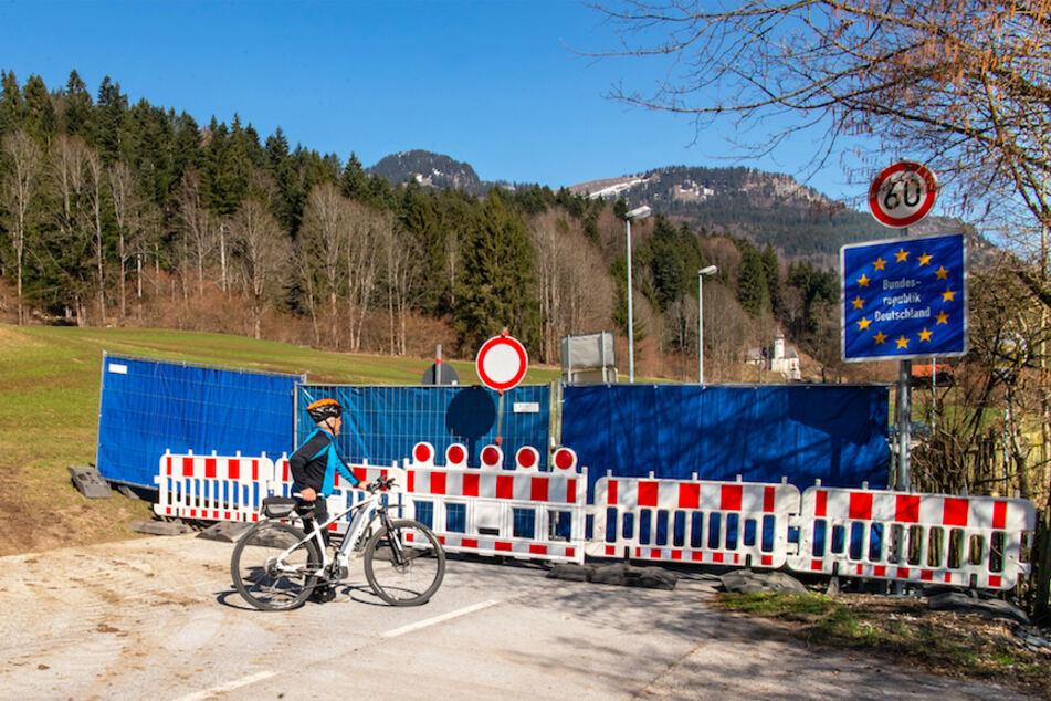 Ein Mann mit einem Mountainbike steht auf der österreichischen Seite vor der mit einem Bauzaun abgesperrten Grenze zwischen Bayern und dem Kufsteinerland in Tirol (Österreich).