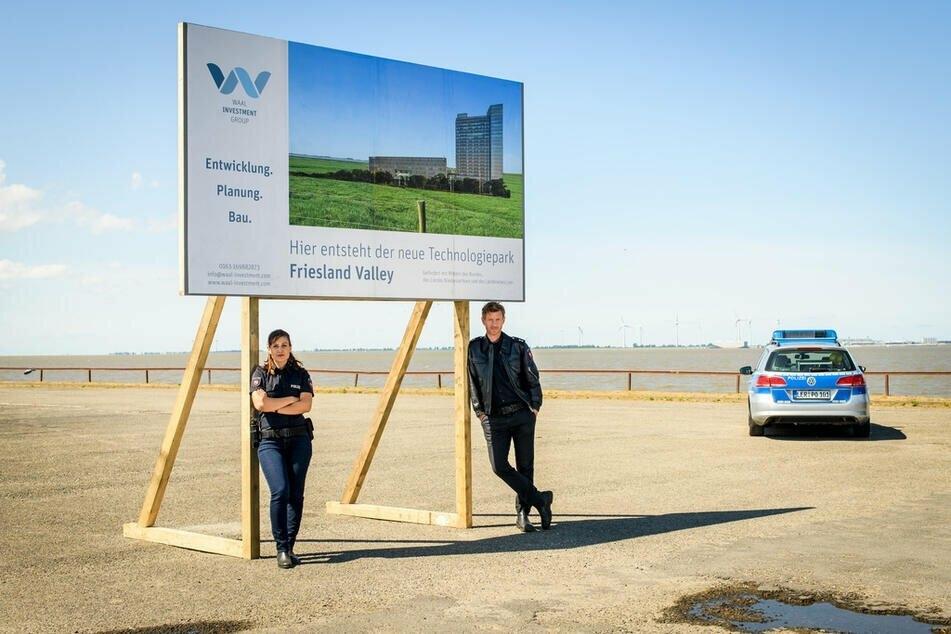 """""""Friesland - Haifischbecken"""": Süher Özlügül (Sophie Dal, l.) und Henk Cassens (Maxim Mehmet, r.) lehnen an einer Plakatwand. Ein """"Silicon Valley"""" soll in Leer entstehen..."""