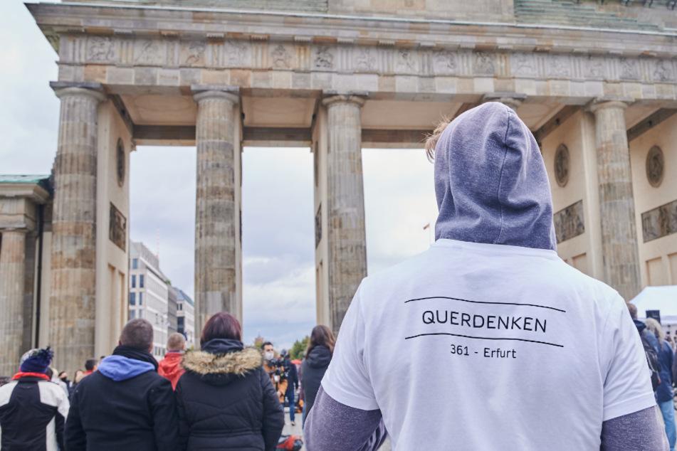 Ein Teilnehmer einer Quederdenk-Demonstration steht vor dem Brandenburger Tor.