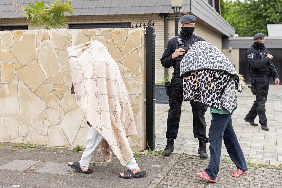 Polizisten stehen vor der Villa der Leverkusener Clan-Familie, während zwei Personen mit Decken über dem Oberkörper das Gelände verlassen.