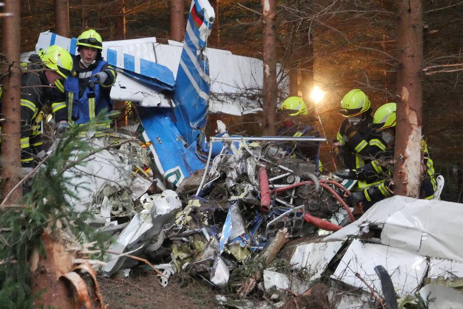 Einsatzkräfte arbeiten am Wrack eines kleinen Flugzeugs, das in ein Waldgebiet gestürzt ist. Vom Piloten oder Co-Piloten fehle noch jede Spur, ein Polizeihubschrauber sei für die Suche im Einsatz, sagte ein Polizeisprecher in Siegen.