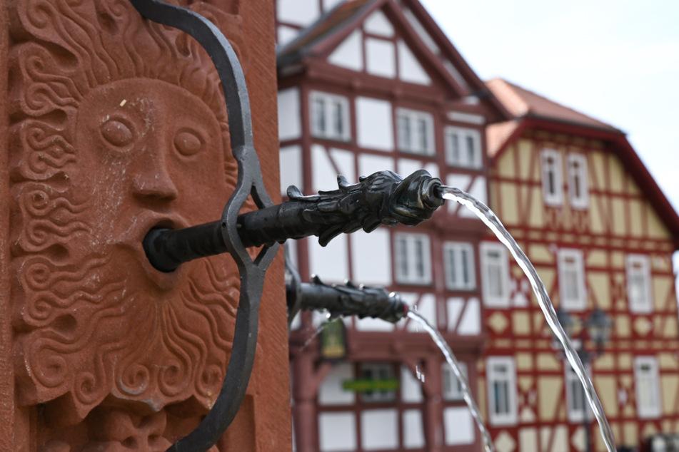 Historische Fachwerkhäuser und ein alter Brunnen sind auf dem Marktplatz des Hessenparks zu sehen, einem beliebten Ausflugsziel im Taunus.