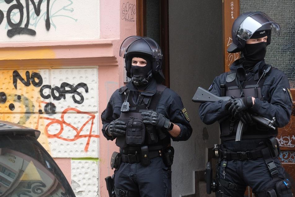 Polizisten stehen vor einem Hauseingang in Connewitz.