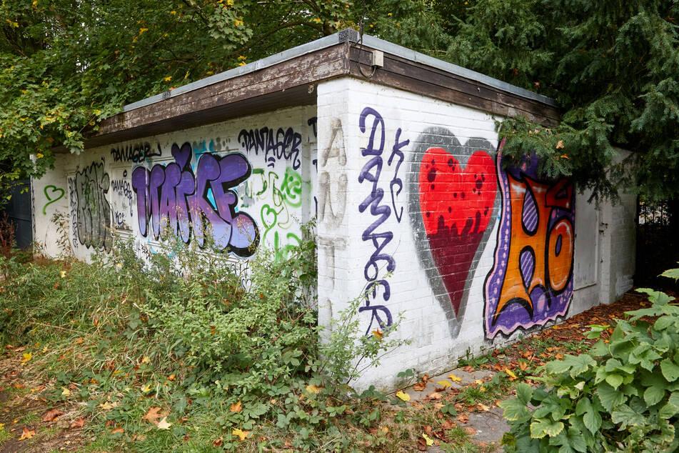 Das leer stehende und mit Graffitis überzogene WC-Häuschen steht auf dem Ohlsdorfer Friedhof.
