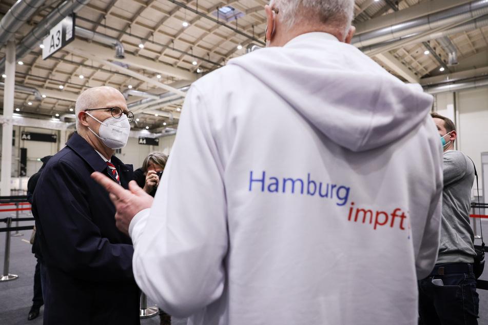 Peter Tschentscher (SPD, l) und Dirk Heinrich, ärztlicher Leiter des Impfzentrum Hamburg, unterhalten sich bei einem Medientermin im Impfzentrum in den Messehallen.