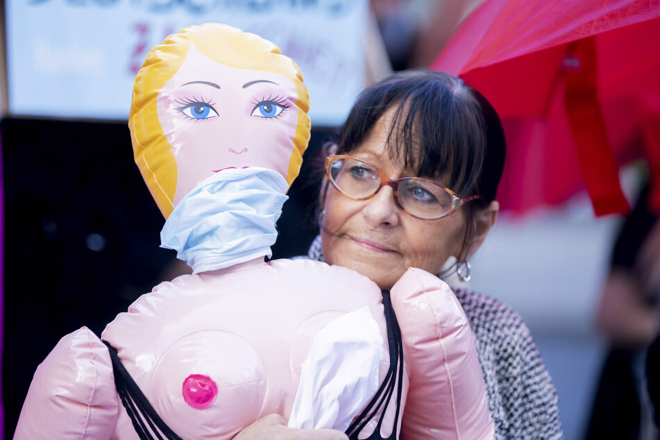 3. Juli, Berlin: Eine Teilnehmerin steht bei einer Protestaktion für die Öffnung von Prostitutionsstätten mit einer Sexpuppe im Arm nahe des Bundesrates. Bordelle sind seit Mitte März auf Grund der Maßnahmen zu Eindämmung des Coronavirus weiterhin geschlossen.