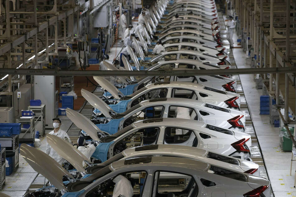 Arbeiter sind in einer Fabrik am Fließband beschäftigt. (Symbolbild)