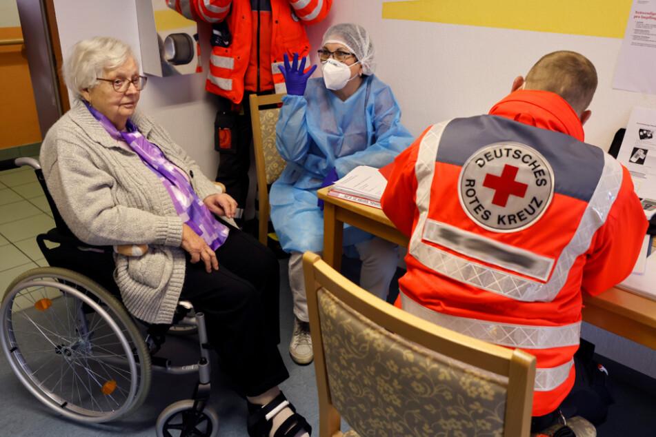 Das Deutsche Rote Kreuz (DRK) spricht mit einer Seniorin, bevor sie ihre Corona-Impfung bekommt. Im Landkreis Sonneberg wird das DRK nun älteren und pflegebedürftigen Menschen helfen, einen Impftermin zu organisieren.