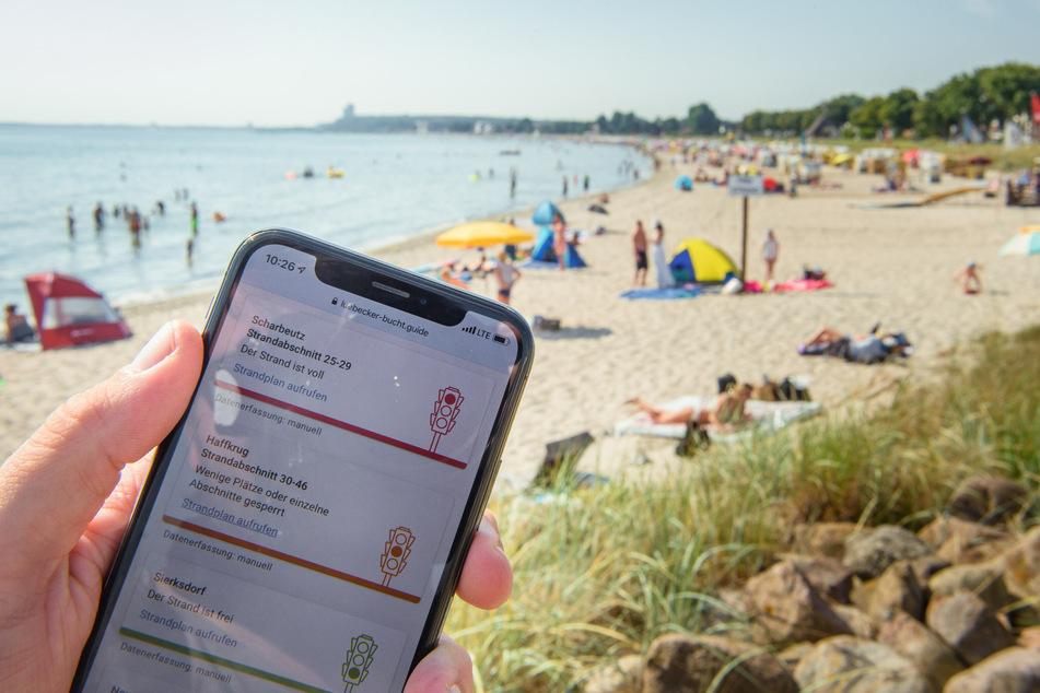 """Die App """"Strandticker"""" der Ostseegemeinden ist vor einem mit Badegästen und Strandkörben gefüllten Strandabschnitt in der Dorfschaft Haffkrug der Gemeinde Scharbeutz zu sehen."""