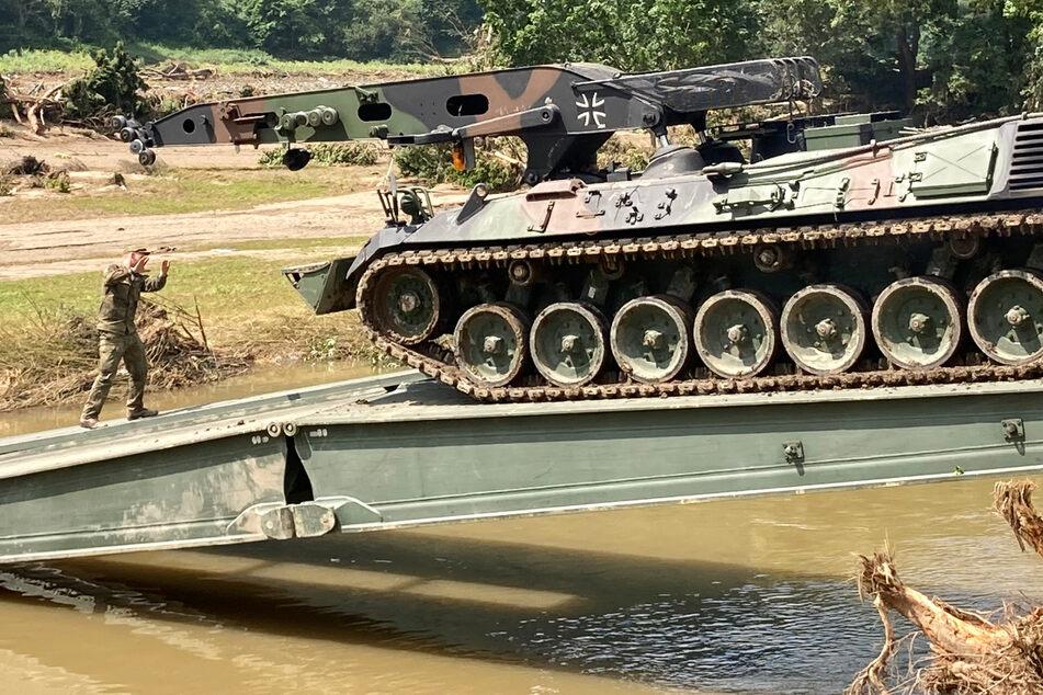 Einsatzkräfte der Bundeswehr bauen eine Behelfsbrücke über die Ahr im Weinort Rech im Landkreis Ahrweiler.