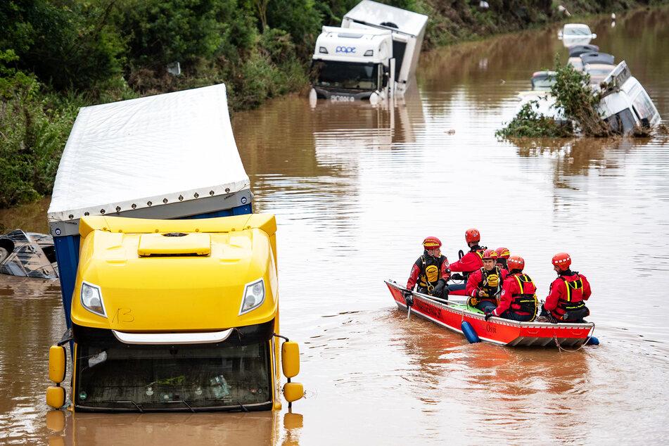 Helfer der Wasserwacht untersuchen von einem Boot aus Lastwagen, die auf einer überfluteten Straße in Erftstadt stehen.