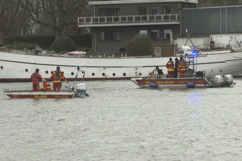 """Rettungskräfte der Wasserrettung DLRG und Polizeitaucher suchen in der Elbe neben dem Binnenschiff """"Lusitania"""" nach einem Matrosen."""