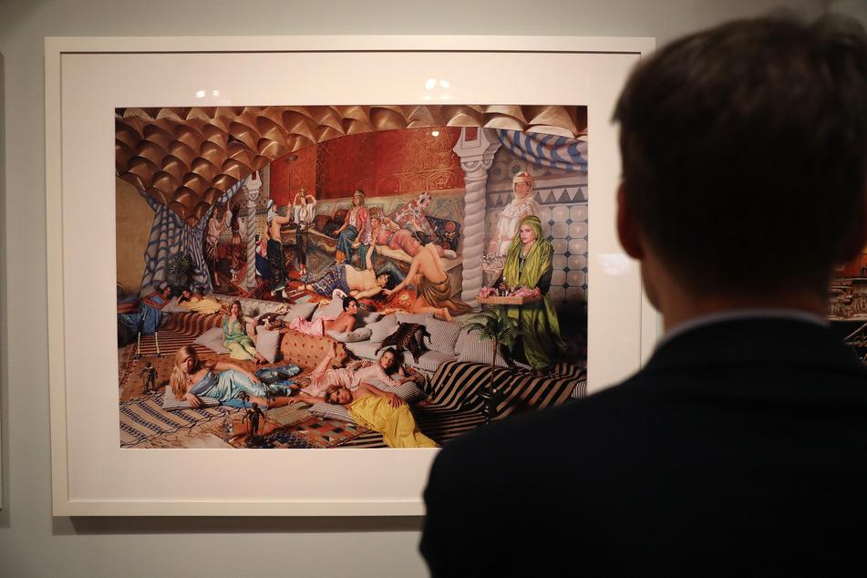 """Ein Mann betrachtet eine Fotografie von Daniela Rossel aus der Serie """"Ricas y Famoses"""" (Reis he und Berühmte)."""