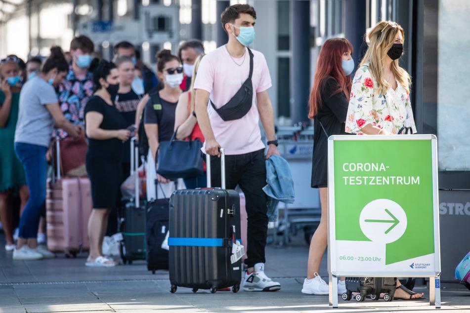 Reiserückkehrer, vorwiegend aus Spanien, stehen mit Mundschutz vor dem Corona-Testzentrum am Flughafen Stuttgart. (Symbolbild)