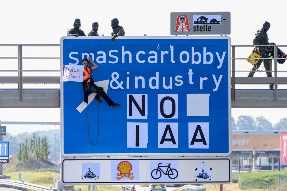 """Ein Aktivist hängt an einer Schilderbrücke über der Autobahn A9 bei Fürholzen in Fahrtrichtung München und hält ein Banner mit der Aufschrift """"Autos zerstören"""" in den Händen, während Polizisten eines Spezialeinsatzkommandos sich auf der Schilderbrücke in Position bringen."""