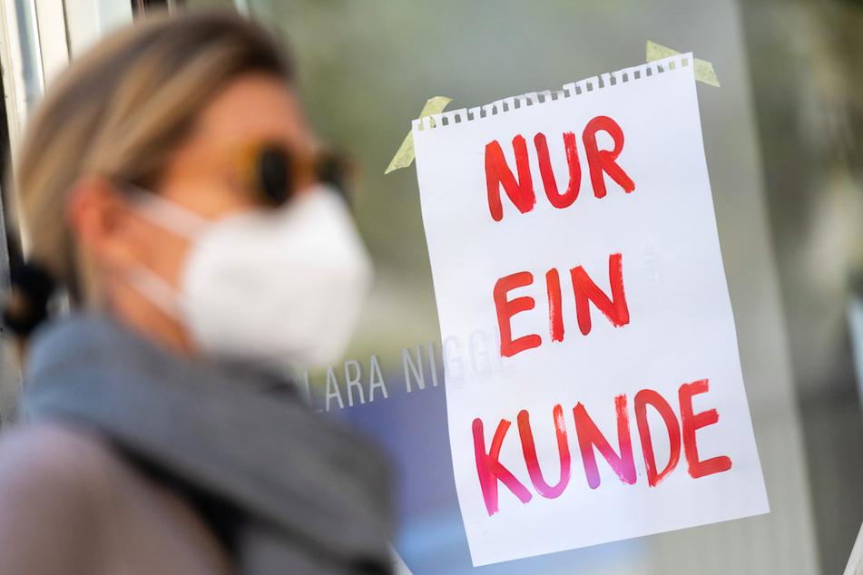 """Eine Frau mit Nase-Mund-Schutzmaske geht an einem Geschäft vorbei, an dem ein Schild mit der Aufschrift """"Nur ein Kunde"""" angebracht ist."""