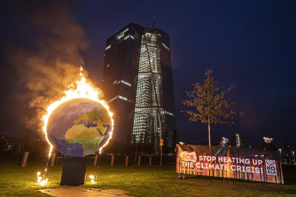 """Mit einer brennenden Erdkugel demonstrieren Aktivisten der Gruppe """"Das Koalakollektiv"""" vor der Europäischen Zentralbank (EZB) in Frankfurt gegen die Klimapolitik des Geldinstituts."""