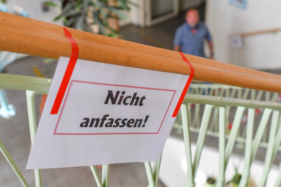 """Ein Zettel mit der Aufschrift """"Nicht anfassen!"""" hängt an einem Geländer einer Grundschule in Eisenhüttenstadt."""