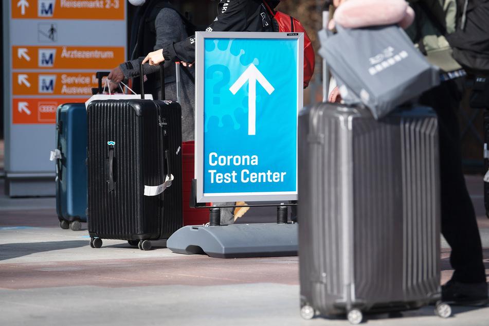 Reisende gehen an einem Flughafen zum Corona-Testzentrum.