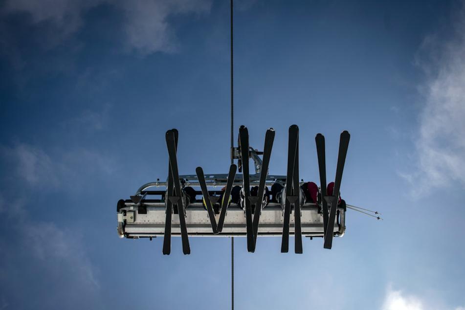 Skier in einem Lift zeichnen sich vor dem blauen Himmel ab.