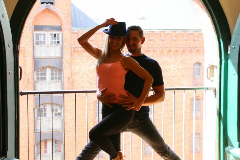 Isabel Edvardsson und Benjamin Piwko posieren vor einem Fenster im Tanzstudio.