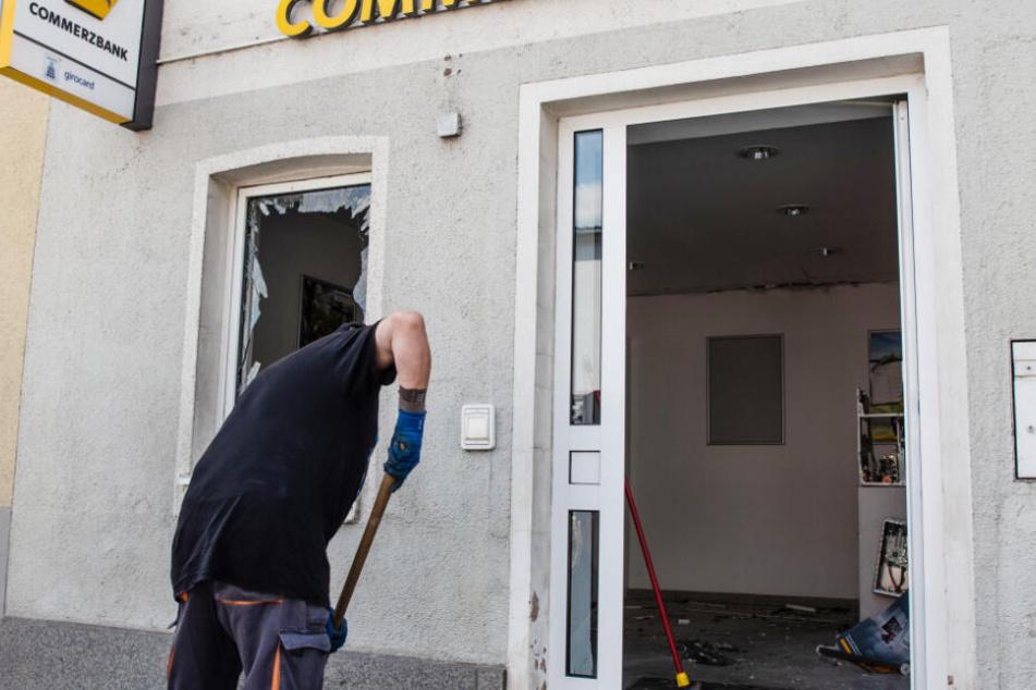 Ein Mann kehrt vor einer Bankfiliale der Commerzbank, in welcher am frühen Morgen ein Geldautomat gesprengt wurde, Scherben einer Fensterscheibe zusammen.