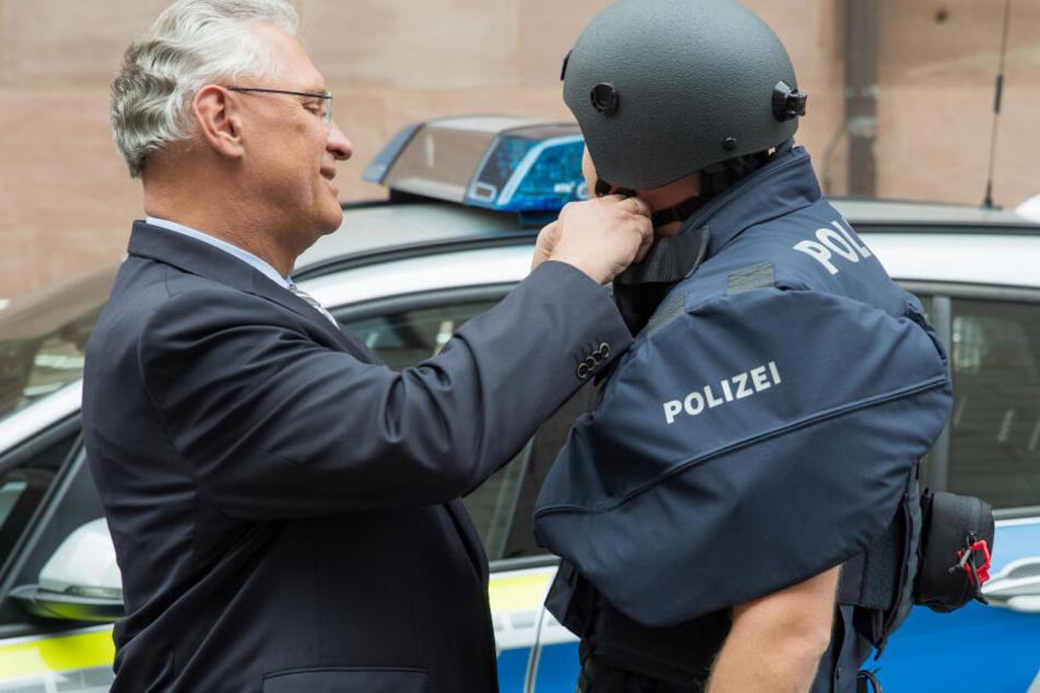 Der bayerische Innenminister Joachim Herrmann (l, CSU) hilft einem Polizisten mit Kugelsicherer Weste der Schutzklasse vier einen neuen ballistischen Schutzhelm zu schließen.