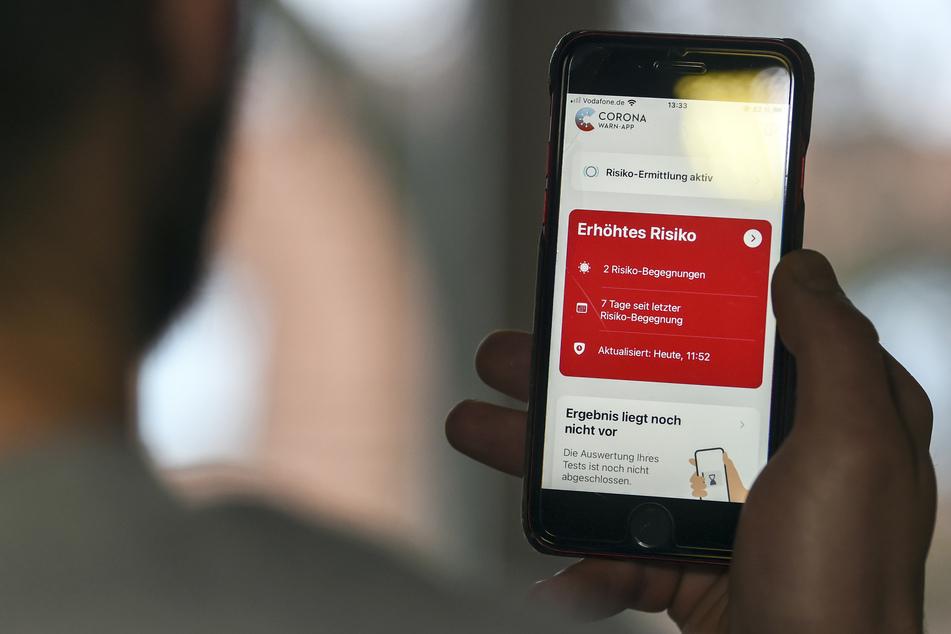 """Auf einem Handy zeigt die """"Corona Warn-App"""" ein erhöhtes Risiko an, welches darauf hinweist Kontakt mit einer infizierten Person gehabt zu haben."""