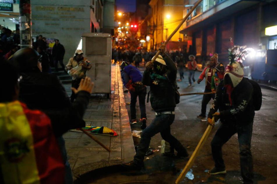 Mit einem Stock versucht ein Anhänger von Präsident Morales auf einen Demonstranten einzuschlagen.