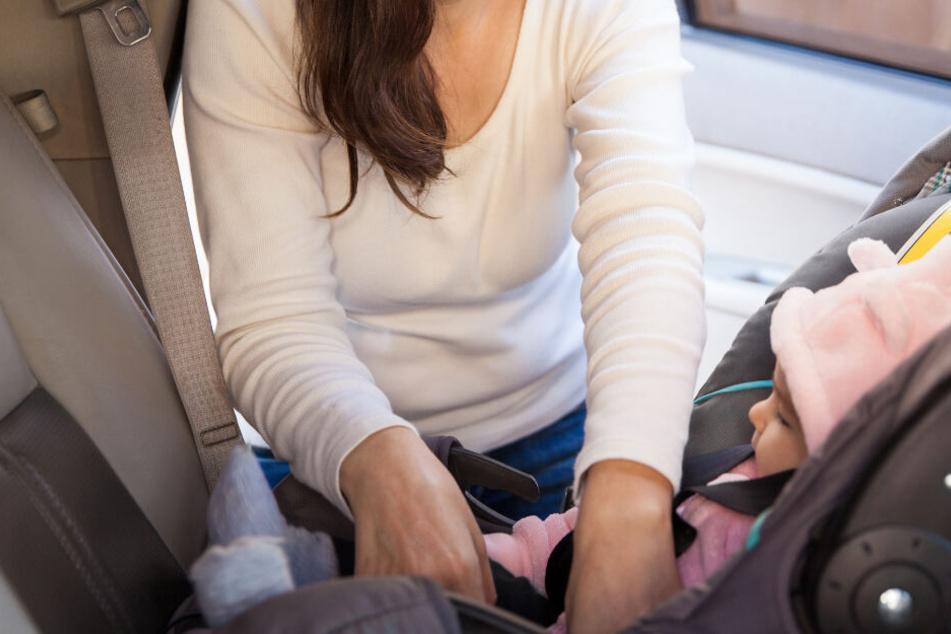 Eine Frau setzt ein Baby im Kindersitz ins Auto. (Symbolbild)