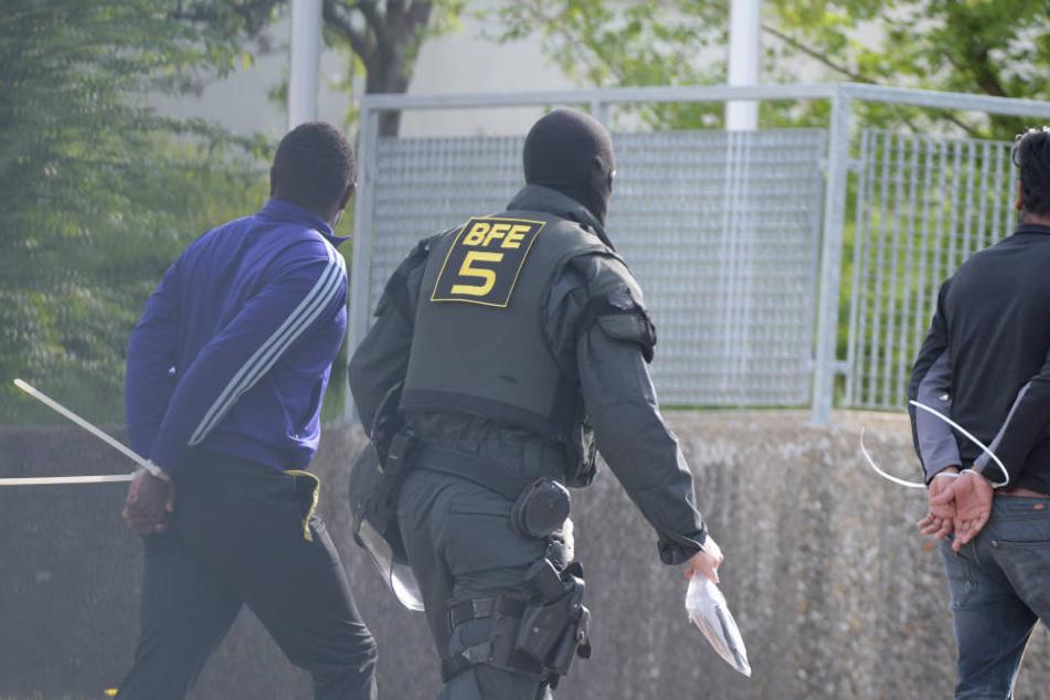 In der Landeserstaufnahmeeinrichtung für Flüchtlinge (LEA) wird zwei gefesselte Männer von einem maskierten Polizisten abgeführt. (Archivbild)