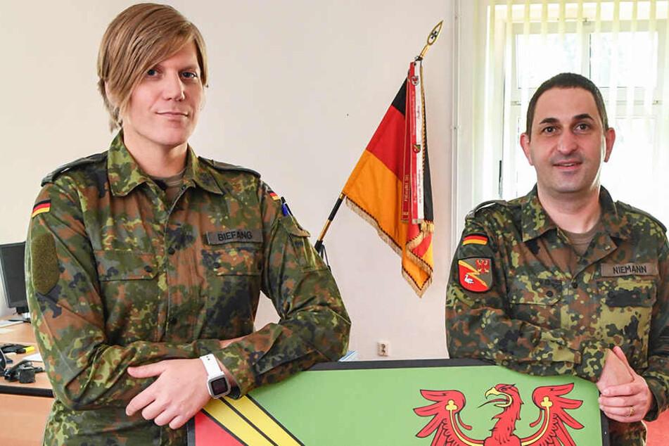 Ein ehemaliger Oberstleutnant (rechts) und seine Nachfolgerin stehen vor dem Wappen der Kurmark-Kaserne.
