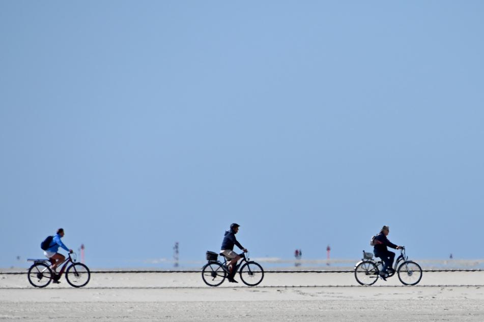 Radfahrer fahren bei blauem Himmel über den Nordseestrand.