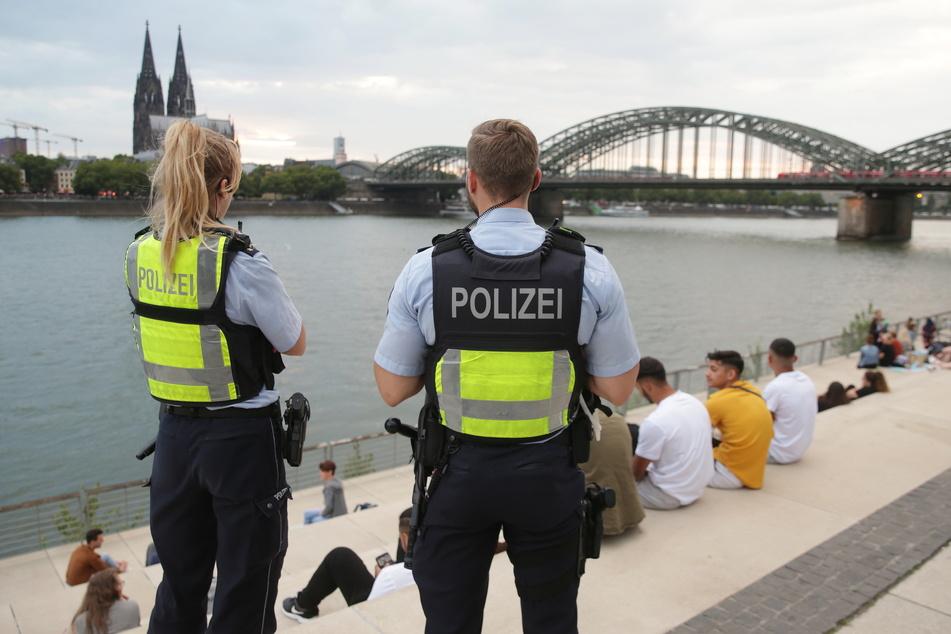 Polizisten und Besucher am Rheinboulevard in Köln.