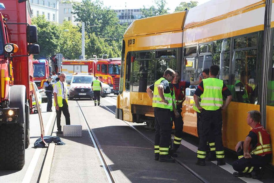 Mitarbeiter der Feuerwehr begutachten die aus den Gleisen gesprungene Bahn.