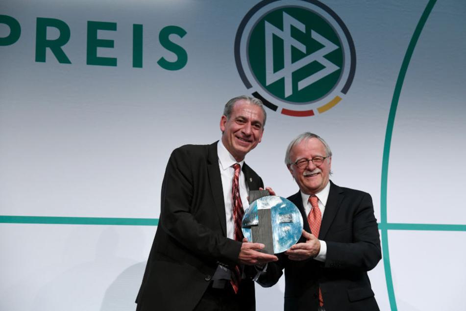 Verani Kartum (li.), der Vereinsvorsitzende vom Preisträger SC Aleviten Paderborn, bekommt den Julius Hirsch Preis von Laudator Hans Leyendecker überreicht.