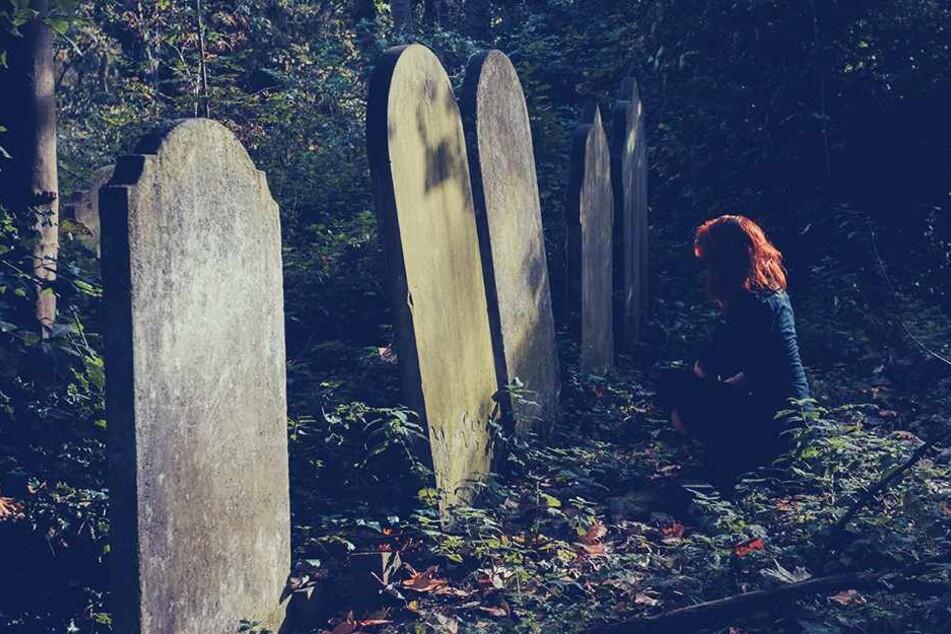 Ein etwa 15 Jahre altes Mädchen weint nachts an einem Grab (Symbolbild).