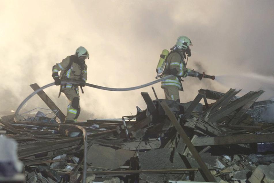 Feuerwehrmänner löschen Flammennester in den Trümmern.