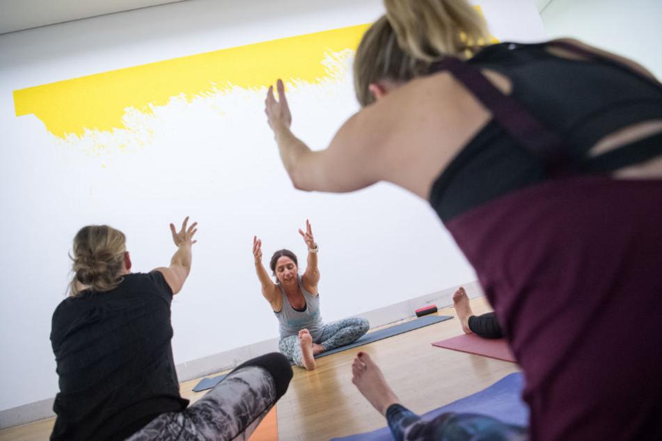 """Yogakurs mit Kunst in Sindelfingen. Im Hintergrund das Werk """"Trevira"""" von Leni Hoffmann."""