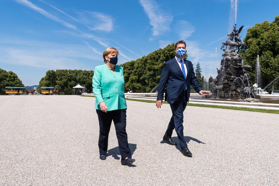 Markus Söder (CSU), Ministerpräsident von Bayern, und Bundeskanzlerin Angela Merkel (CDU) gehen nach einer gemeinsam Kutschfahrt zur Kabinettssitzung.