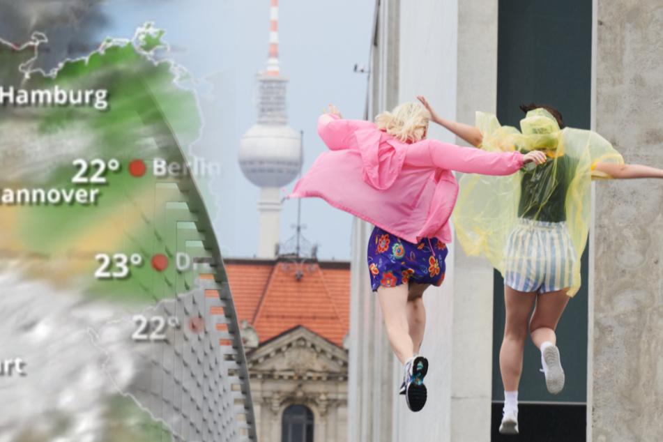 Zwei junge Frauen springen nach einem Regenguss mit bunten Regencapes über den Marie-Elisabeth-Steg am Paul-Löbe-Haus.