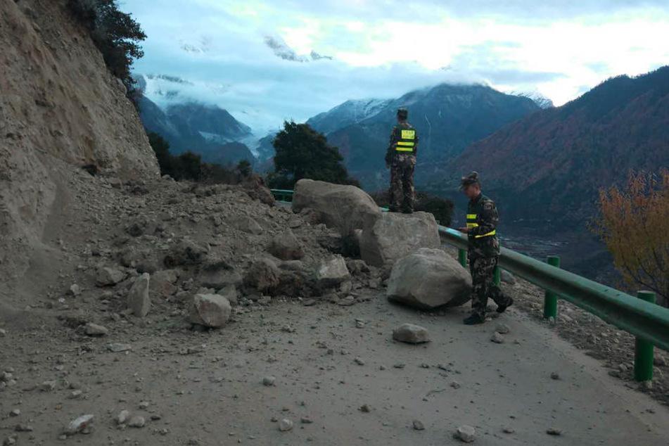 Eine Straße im Kreis Mainling im autonomen Gebiet Tibet ist nach einem Erdbeben durch herabgestürzte Felsbrocken blockiert.
