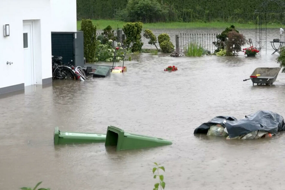 Nach einem Starkregen ist der Vorgarten eines Hauses in Bayern überschwemmt.