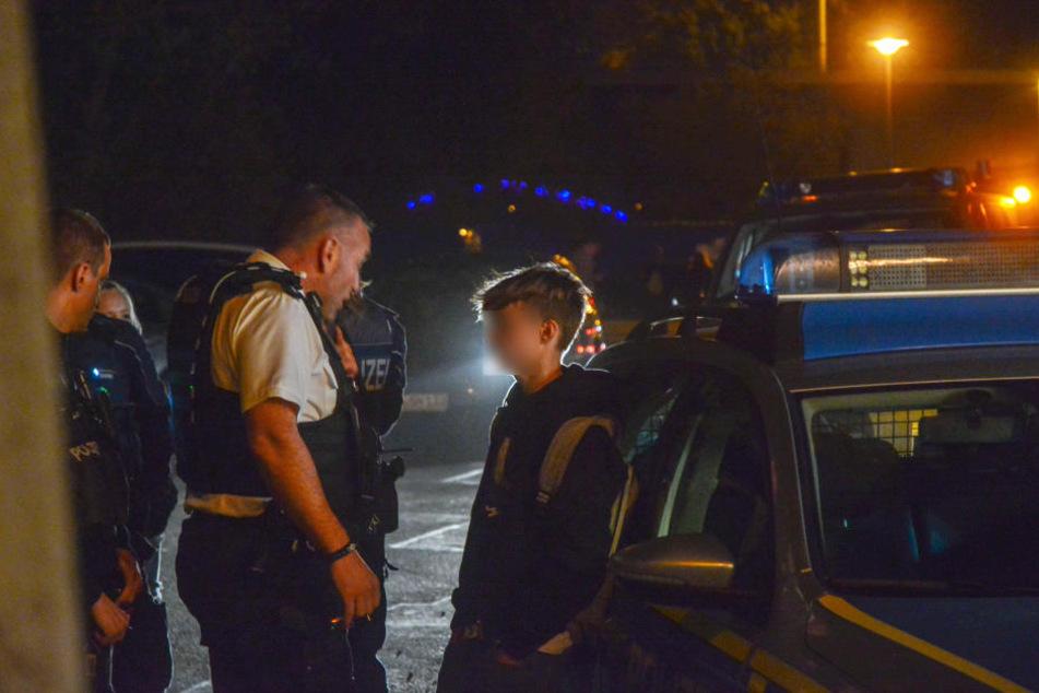 Polizeibeamte weisen einen der Jugendlichen zurecht.